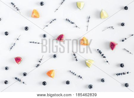 blueberry, citrus, lavender flowers design on white wooden desk background top view pattern