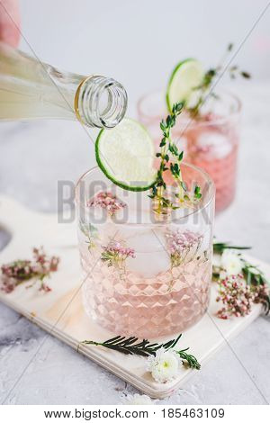 fresh homemade drink with flowers and sliced lime on kitchen table background