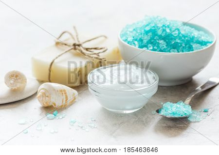 natural blue bath salt, body cream and shells for spa on white table background