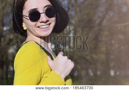 A Joyful Girl In A Bright Yellow Sweater Walks Through The Spring Forest