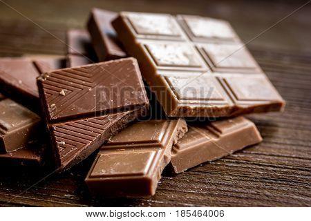 chopped chocolate pieces for dessert on dark wooden desk background