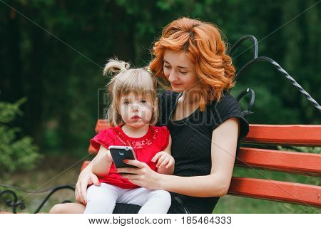 mother and her little daughter sitting on a park bench and enjoy the phone