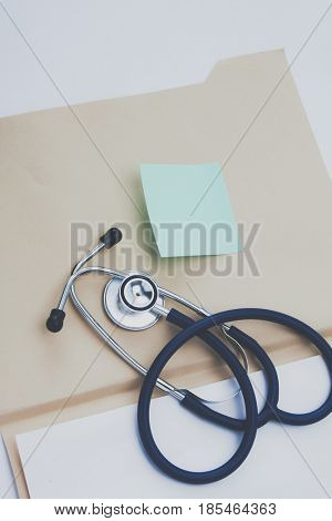 Afile folder, a stethoscope and a pen on ekg