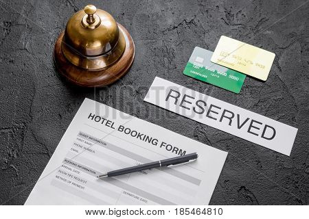 booking hotel room application form and ring on dark desk background