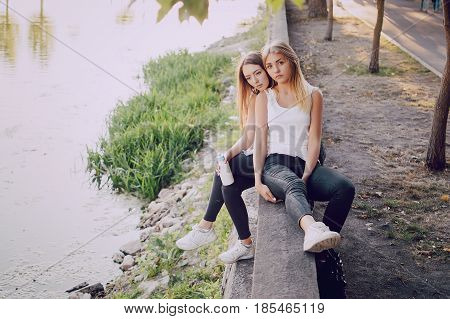 Two beautiful girls sitting in the park by the river