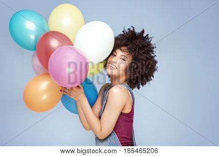 Happy Young Girl With Afro Holding Balloons.