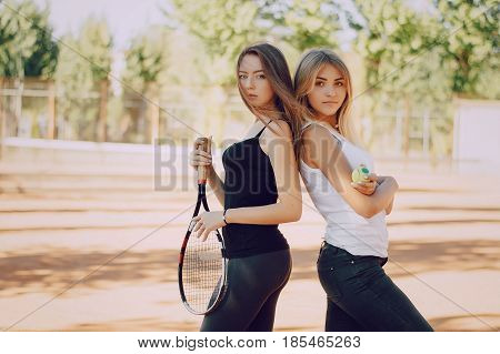 girl standing at the tennis nets and holding a tennis racket and ball