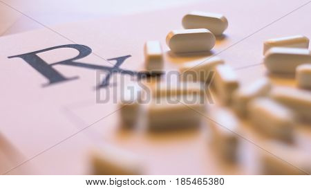 Prescribing overprescribing prescription pills concept with blank RX form and falling tablets close up in natural light shallow DOF.