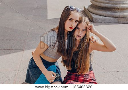 Two beautiful girl with long hair in a summer city with skateboard