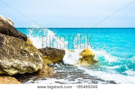 ocean waves from the Mediterranean Sea crashing & splashing on rocks. The water is a beautiful vibrant turquoise color. Taken on a beach of Nice a city in the Cote d'Azur (French Riviera) France.