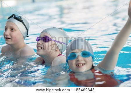 young and successful swimmers pose in swimming pool