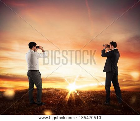 Businessmen leaning on a mountain watching sunset panorama with binoculars