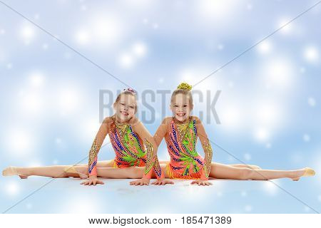 Two adorable little twin girls, gymnastics in the sports school. Girls beautiful gymnastic leotards. They do the splits.Blue Christmas festive background with white snowflakes.