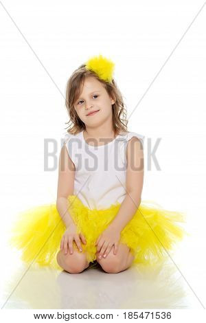 Pretty little blonde girl in a short bright yellow skirt and white blouse.She kneels and gently looking at the camera with folded hands near the face.Isolated on white background.