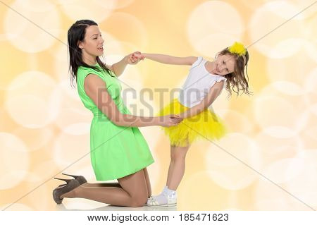 Beautiful young mother in a short green dress and her little beloved daughter in a yellow skirt.They have fun holding hands.Brown festive, Christmas background with white snowflakes, circles.
