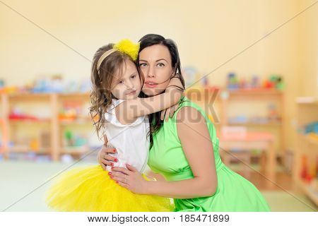 Beautiful young mother in a short green dress and her little beloved daughter in a yellow skirt.Daughter gently hugs the mother's neck.In the Montessori Room the children's garden.