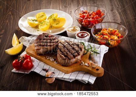 Grilled beefsteaks on cutting board - dinner preparation