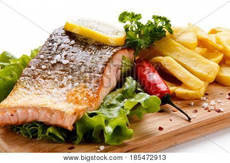 Grilled salmon with french fries on cutting board