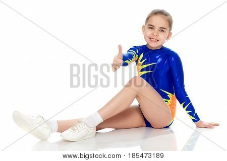 A charming gymnast girl, a younger school age, in a beautiful blue swimsuit, performs an exercise on the floor.She looks directly into the camera.Isolated on white background.