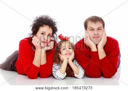 Happy young family dad mom and a little girl in bright red outfits . Family lying on the floor leaning on his hands.Isolated on white background.