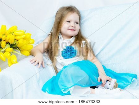 Cute little girl with long blond hair in a long blue skirt sitting on the couch with a large bouquet of bright yellow tulips.