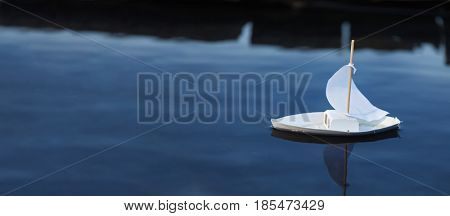 White toy boat at a pier in a pond in summer
