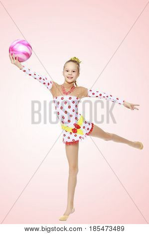 Beautiful little girl gymnast dressed in sports suits for competition, performs exercises with the ball.Pale pink gradient background.
