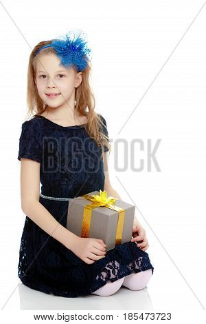 Cute Caucasian little girl In a dark blue dress and big blue bow on her head. The girl holds box with gift.Isolated on white background.