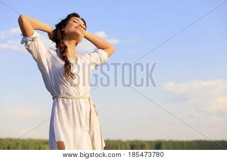 Young happy woman in green field, blue sky behind