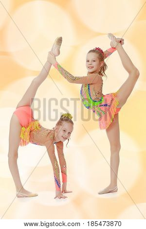 Two adorable little twin girls, gymnastics in the sports school. Girls beautiful gymnastic leotards. They do the splits.Brown festive, Christmas background with white snowflakes, circles.