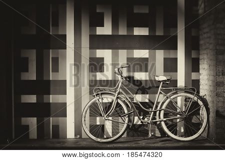 Vintage bicycle against a wall with geometric pattern.  Picture in sepia