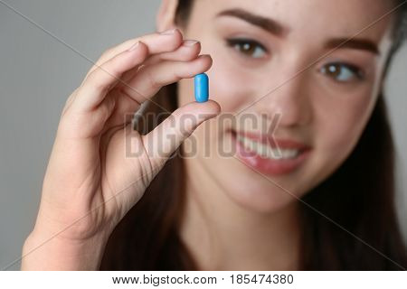 Beautiful young woman with pill on light background, closeup