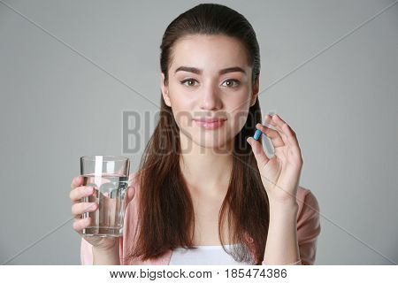 Beautiful young woman with pill and glass of water on light background