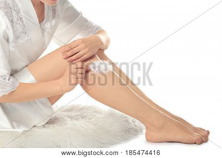 Young woman touching leg with feather on white background