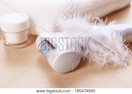 Modern epilator and feather on wooden table, closeup