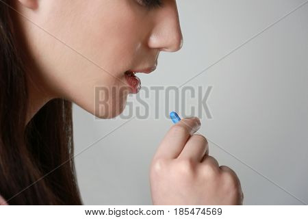 Beautiful young woman taking pill on light background, closeup