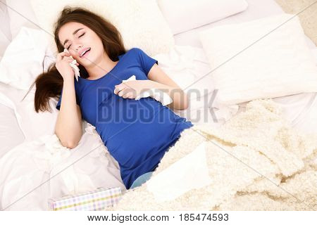 Young pregnant woman lying in bed at home