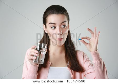 Funny young woman with pill and glass of water on light background