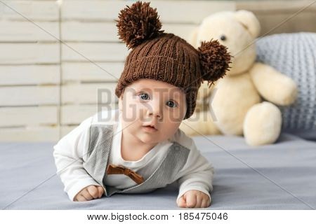 Cute little baby in funny hat lying on soft blanket