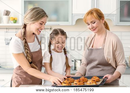 Happy family with tasty buns in kitchen