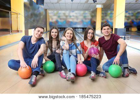 Friends sitting on floor in bowling club