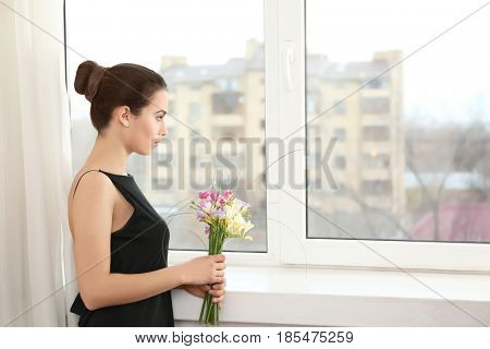 Beautiful young woman with bouquet of flowers near window at home