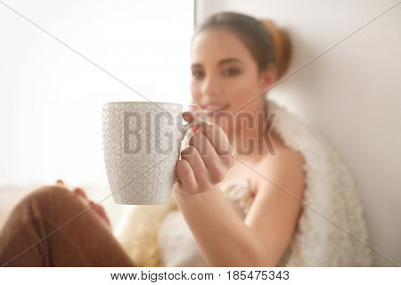 Beautiful young woman with cup of coffee sitting on window sill at home