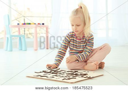 Cute little girl playing with letters while sitting on floor at home