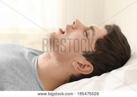 Handsome young man sleeping in bed at home