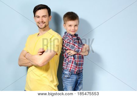 Handsome man and his son on color background