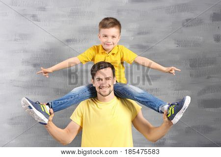 Handsome man and his son near color wall