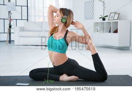 Woman doing yoga and listening to the music at home