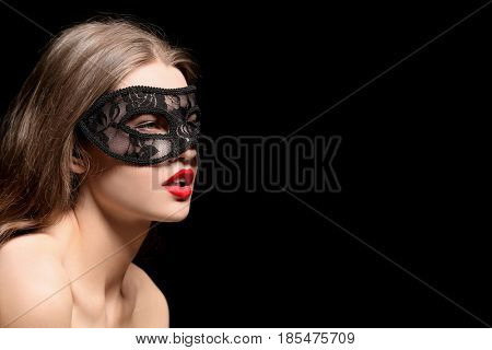 Sexy beautiful woman with carnival mask on black background