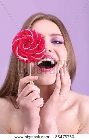 Portrait of beautiful young woman with lollipop on color background